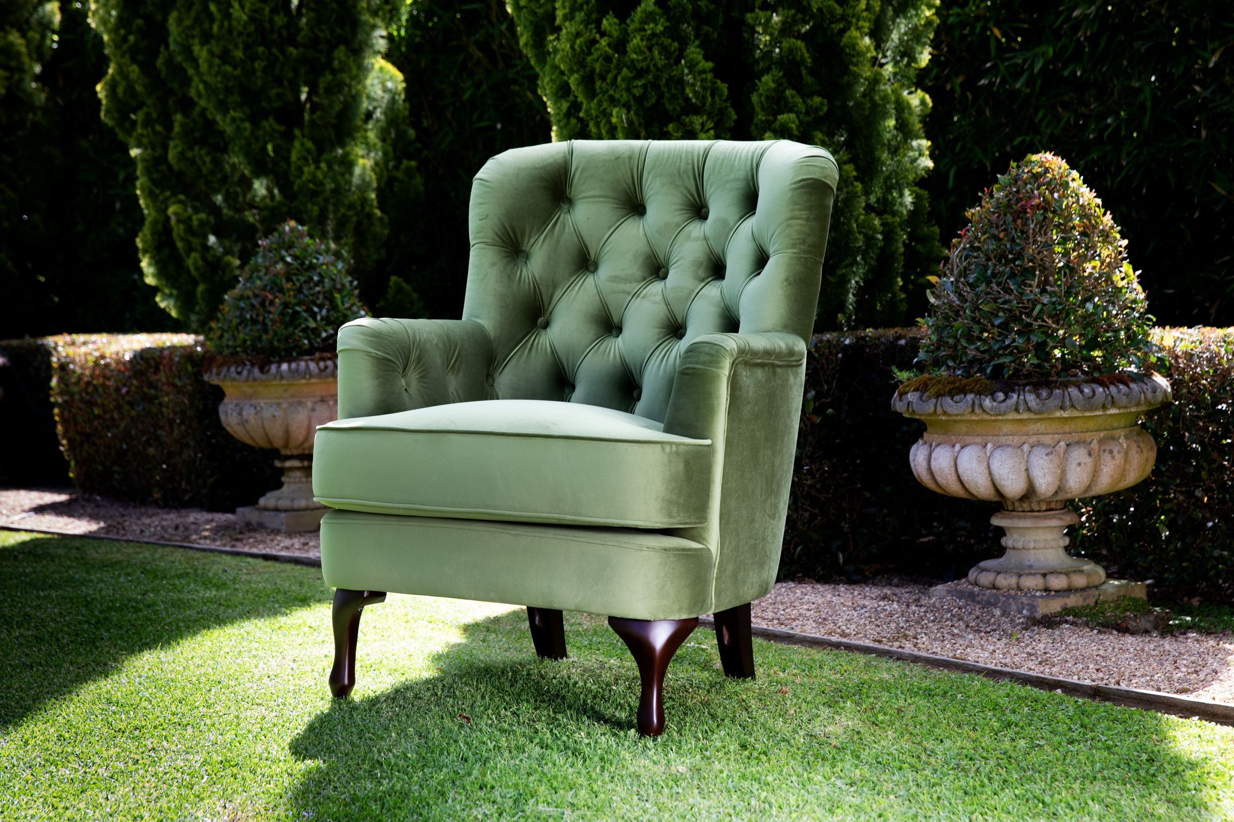 Fully upholstered green velvet chair with deep button back and cabriole leg.