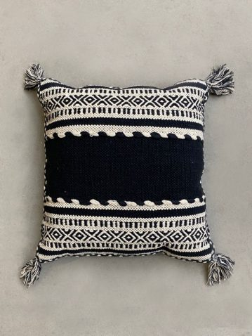 black and white knitted cushion with tassels