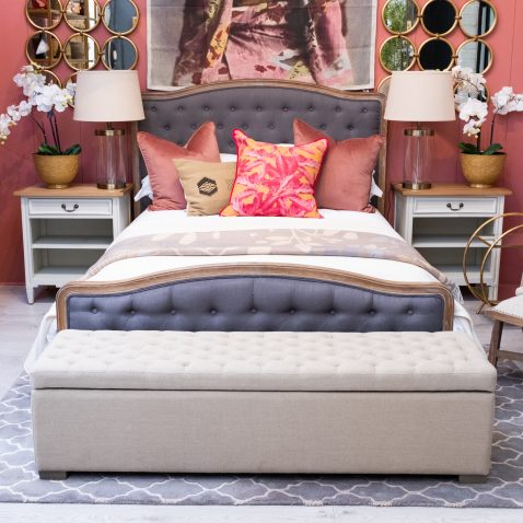 Wooden frame French style bed upholstered in charcoal fabric with deep button detail.