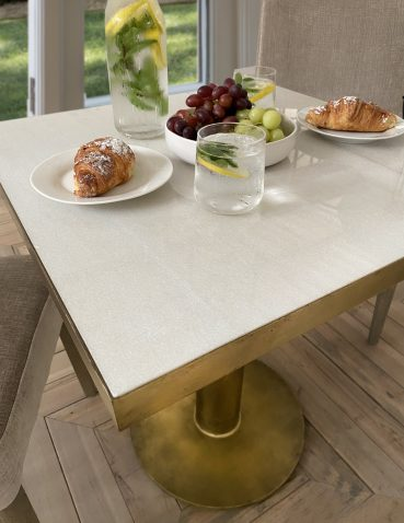 Gold tall side table with round brass base and square marble top.