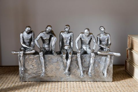 Silver figures on a shelf waiting and contemplating decor