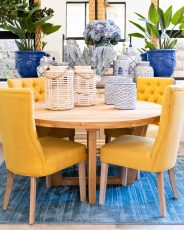 Upholstered yellow dining chair with button back detail and wooden legs.