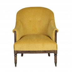 Deconstructed occasional chair with castors, upholstered in a mustard fabric.