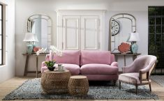 3 seater dusty pink upholstered sofa with oak wooden legs.