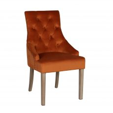 Burnt orange, buttoned back, upholstered dining chair with metal ring detail at the back.