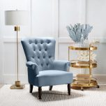 blue velveteen armchair with high tufted back and wooden legs