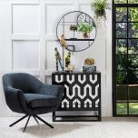 Swivel tub chair with black metal legs upholstered in a charcoal fabric.