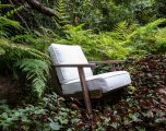 Wooden frame lounge chair with loose cushions upholstered in a ivory fabric.